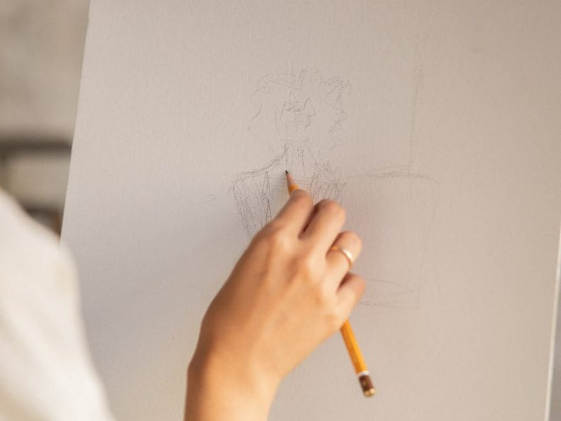 person drawing on white paper